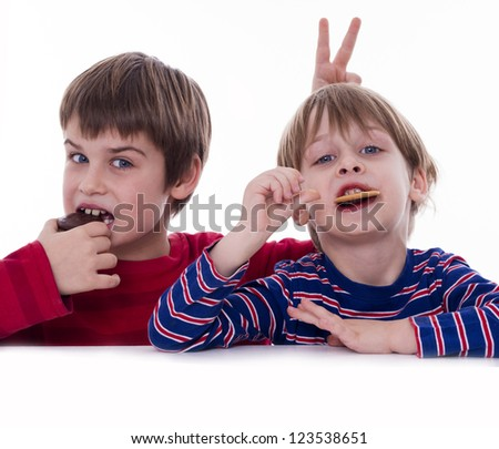 two boys eating cookies
