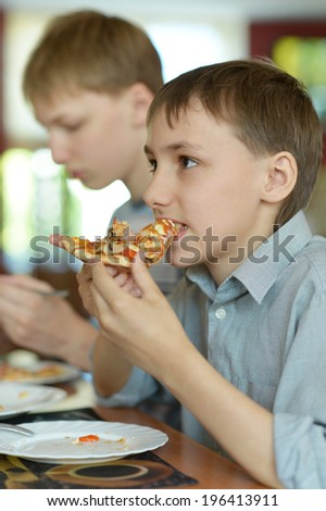 Two boys eatning pizza in cafe together