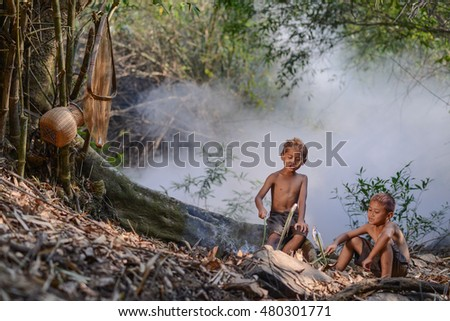 Two boys fish grilled on the fire in the forest.