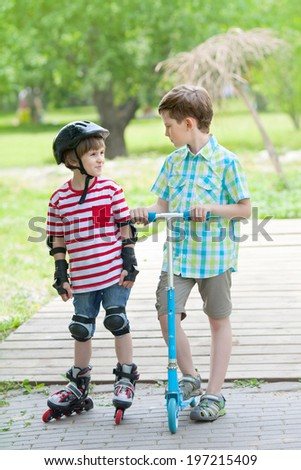 two boys go for a drive on scooter and rollers in the city Park - stock photo