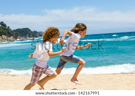 Two boys having a race on sunny beach.