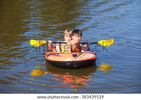Two Boys Having Fun on Inflatable Rubber Boat in Summer - stock photo