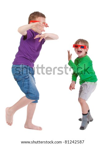 two boys having fun wearing 3D glasses on white background - stock photo