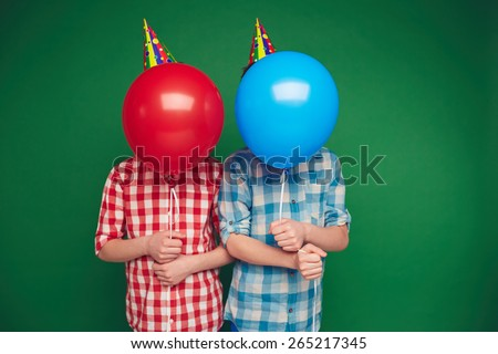 Two boys hiding behind red and blue balloons - stock photo