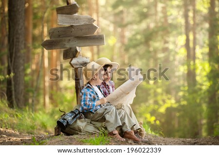 Two boys hiking with backpacks on a forest road bright sunny day - stock photo