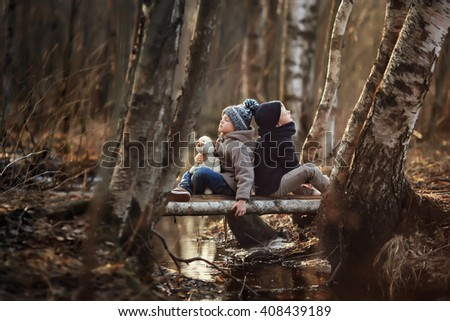 Two boys in hats coat and jeans sitting on the bridge with a toy puppy near a stream in the spring forest - stock photo