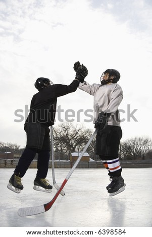 Two boys in ice hockey uniforms giving eachother high five on ice rink. - stock photo