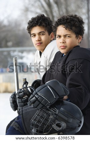 Two boys in ice hockey uniforms sitting on ice rink sidelines looking. - stock photo