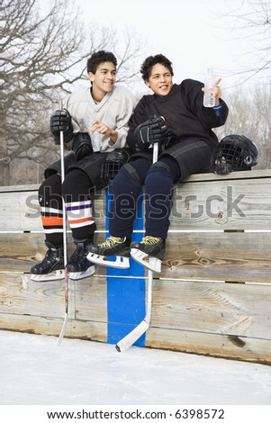 Two boys in ice hockey uniforms sitting on ice rink sidelines pointing and looking. - stock photo