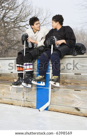 Two boys in ice hockey uniforms sitting on ice rink sidelines talking to eachother. - stock photo