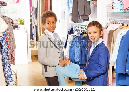 Two boys in suits hold clothing item at the shop - stock photo
