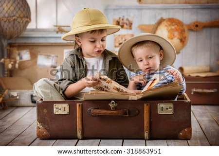 Two boys in the form of tourists see photos from his travels sitting in suitcase - stock photo