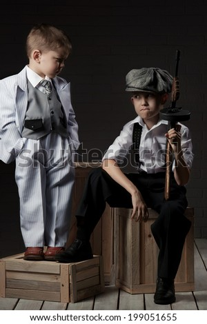 Two boys in the image of gangsters with guns sitting on boxes in stock - stock photo