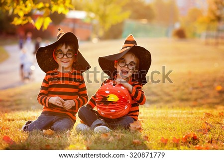 Two boys in the park with Halloween costumes, having fun - stock photo
