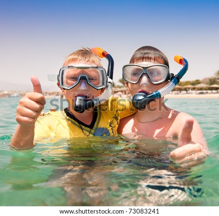 Two boys in the sea on a beach - stock photo