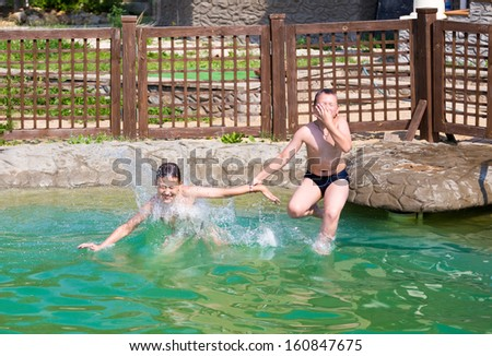 Two boys jump into the pool. Horizontal image - stock photo