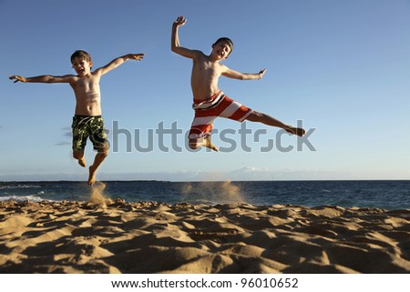 two boys jumping at the beach