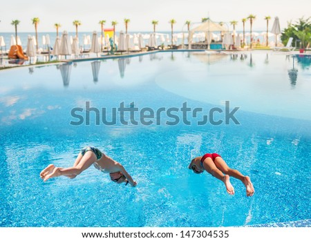 Two boys jumping into a swimming pool