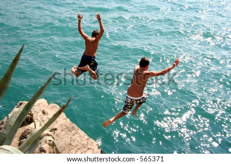 Two boys jumping into water from a rock - stock photo
