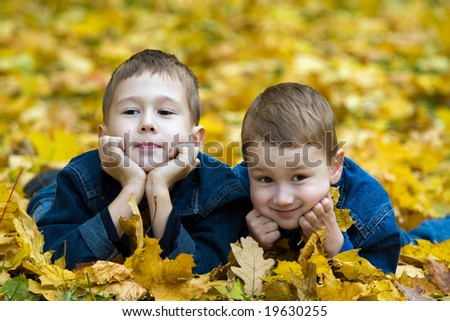 Two boys lay in the fallen autumn foliage - stock photo