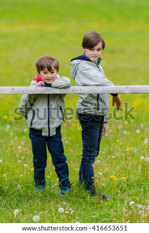 Two boys leaning over a rustic wooden fence