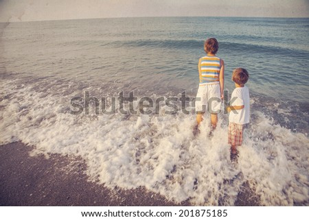 two boys looking at sea - stock photo