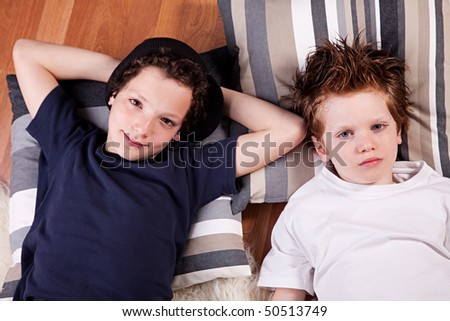 two boys lying on the floor with his head resting on two pillows - stock photo