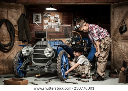 Two boys Mechanical inflated tire on the retro car in the garage - stock photo