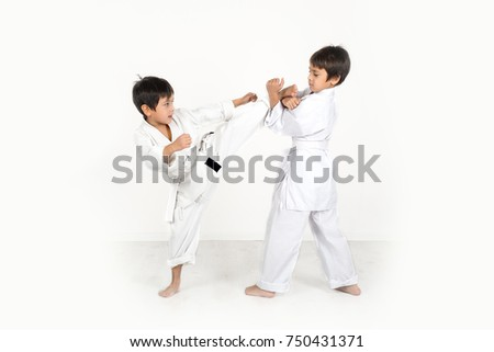 two boys of the karate in a white kimono battle or train