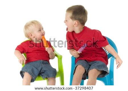Two boys on lawn chairs enjoying popsicles - stock photo