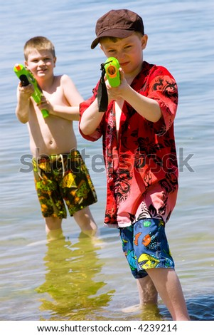 Two boys on the beach with their water guns... ready for a fight - stock photo
