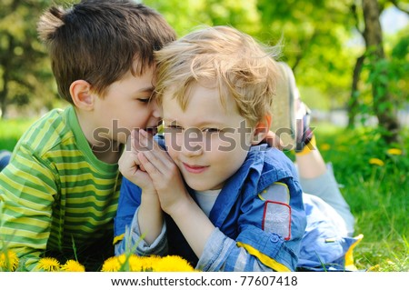 Two boys on the green grass in the park - stock photo