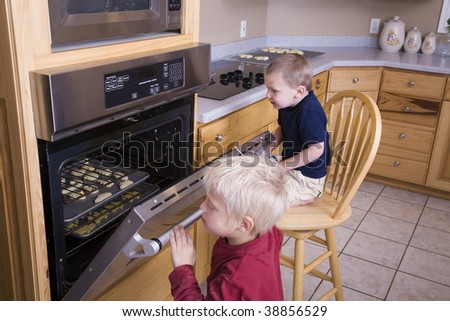 Two boys peeking in the oven at the cookies.