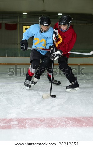 Two Boys play a Winter Hockey Scrimmage in Rink - stock photo