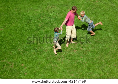 Two boys play with the adult a lawn. The top view. - stock photo