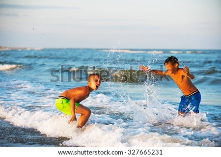 Two boys playing at the beach with water. Big splashes - stock photo