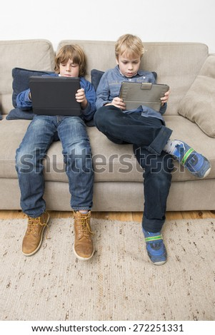 Two boys, playing games on electronic tablets, slouching on a couch, being bored, and acting individualistic - stock photo