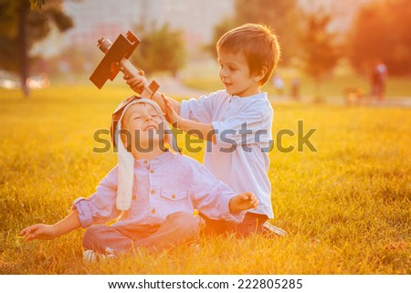 Two boys, playing with airplane on sunset in the park - stock photo