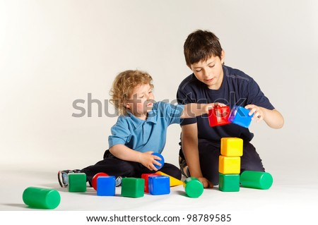 two boys playing with cubes - stock photo