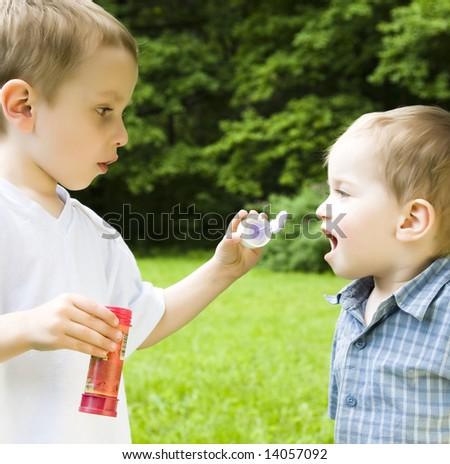 Two Boys Playing With Soap Bubbles - stock photo