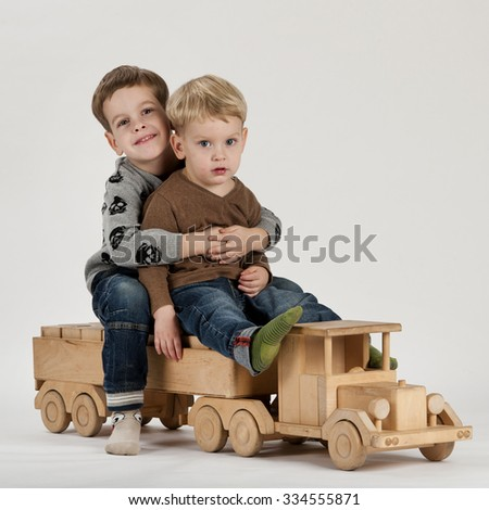 Two boys posing in studio on a big wooden toy car - stock photo