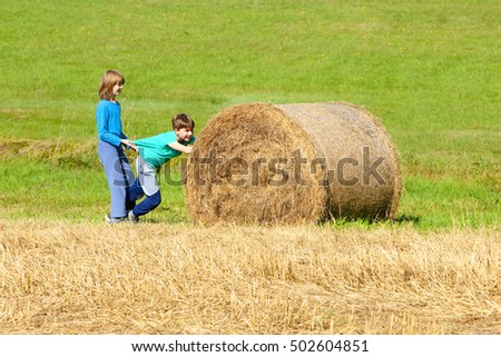 Two Boys Pushing Bale of Hay