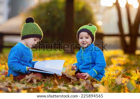 Two boys, reading a book on a lawn in the afternoon, eating snacks, autumn sunset time - stock photo