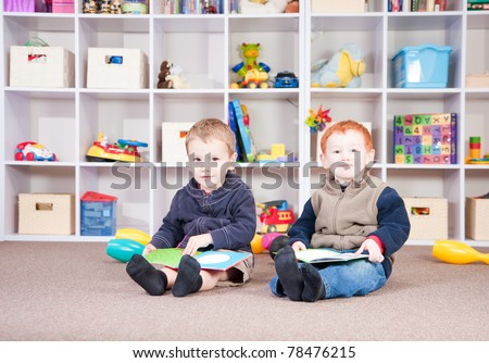 Two boys reading books in play room.