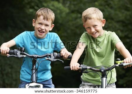 Two Boys Riding Bikes Together - stock photo