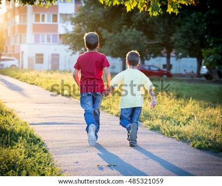 Two boys running together on street with sun back light
