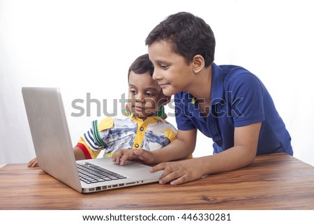 Two boys sharing their laptop on wooden table