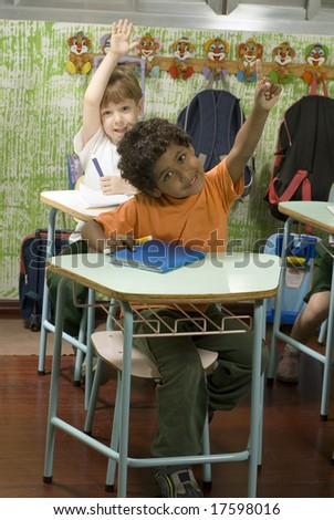 Two boys sitting at desks in a classroom.  They have their hands raised.  They are smiling and are looking at the camera.  Vertically framed shot. - stock photo