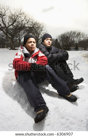 Two boys sitting in snow wearing coats and hats. - stock photo
