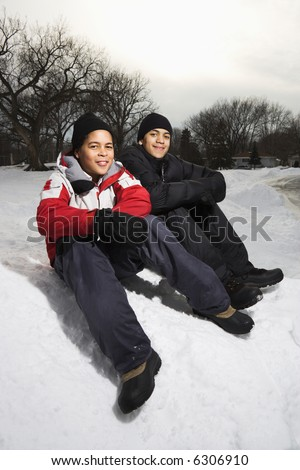 Two boys sitting in snow wearing coats and hats and smiling. - stock photo